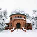 A building surrounded by snow and trees at Observatory Park in Denver.