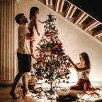Image of a young family decorating a Christmas tree.